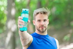 Man with athletic appearance holds bottle with water. Man athlete in sport clothes training outdoor. Sport and healthy. Lifestyle concept. Athlete drink water Stock Photo