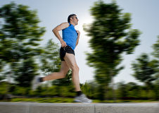 Man with athletic legs running in city park with trees on the background on summer training session fitness healthy lifestyle conc Stock Photo