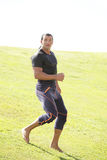 Man in an athletic running pose Stock Photos