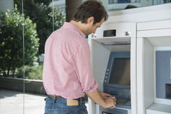 Man atm cash withdraw. Man on atm getting cash Royalty Free Stock Images