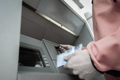 Man at ATM machine with stash of credit and debit cards Stock Photo