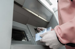 Man at ATM machine with stash of credit and debit cards Royalty Free Stock Images