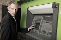 Man at an atm maching glancing over his shoulder. Man glancing over his shoulder at an atm machine Royalty Free Stock Images