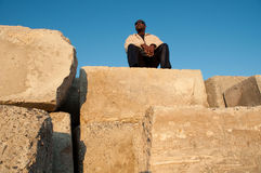 Man Atop Pile of Cement Blocks Stock Image