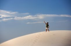 Man atop sand dune pointing at the sky Royalty Free Stock Photo