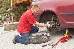 Man att ändra det punkterade däcket på hans bil som lossar muttrarna med en hjulskruvnyckel, innan du silar upp medlet Royaltyfri Foto