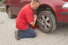 Man att ändra det punkterade däcket på hans bil som lossar muttrarna med en hjulskruvnyckel, innan du silar upp medlet Royaltyfri Bild