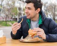 Man att äta en hamburgare med stekte potatisar i gatamatkafé Royaltyfri Foto