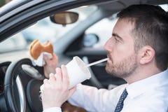Man att äta en hamburgare och körning som placeras i bil Arkivfoton