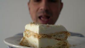 Man att äta en kaka, closeupen, steadycamskottet, den hungriga gick ut munnen som slickar kanter arkivfilmer