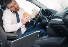 Man att äta fettbildande mat och arbete som placeras i bil arkivbilder