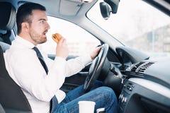 Man att äta fettbildande mat och körning som placeras i bil arkivfoto