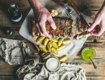 Man att äta grillade grisköttstöd med vitlök, rosmarin, potatis sås arkivbild
