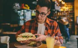 Man att äta i en restaurang och att tycka om läcker mat Royaltyfri Bild