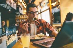 Man att äta i en restaurang och att tycka om läcker mat Arkivfoto