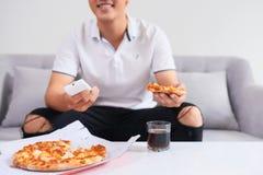 Man att äta pizza som har takeaway hemmastatt koppla av vila royaltyfri foto
