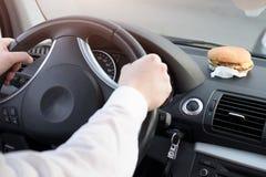 Man att äta skräpmat och körning som placeras i bil arkivfoton