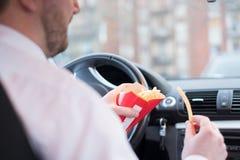 Man att äta skräpmat och körning som placeras i bil royaltyfria bilder