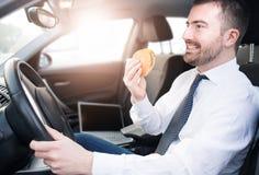 Man att äta skräpmat och körning som placeras i bil fotografering för bildbyråer