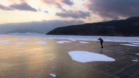 Man att åka skridskor på isen av djupfrysta Lake Baikal under härlig solnedgång stock video