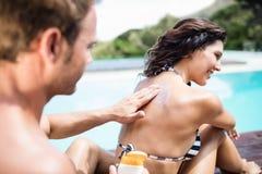Man att applicera sunscreen på baksida av hennes woman arkivfoton