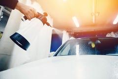 Man att arbeta ett biltvättslut upp bilrengöringar arkivfoton