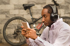 Man att bära den vita röda affärsskjortan som ner på sitter, hörlurar och att se minnestavlaskärmen med intensiv stirrande, cykel arkivfoton