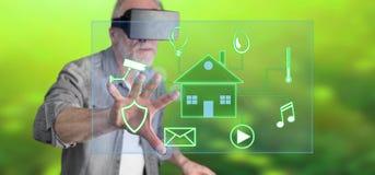 Man att bära en faktisk hörlurar med mikrofon för verklighet som trycker på ett digitalt smart begrepp för hem- automation på en  royaltyfria bilder