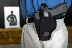 Man att bära en handeldvapen i en sadelgjordsvävpistolhölster royaltyfri bild