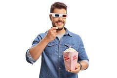Man att bära ett par av exponeringsglas 3D och att äta popcorn Arkivfoto