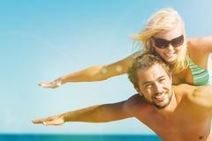 Man att bära hans fru på stranden i semester Arkivbild