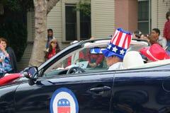 Man att bära 4th av den Juli hatten i bil med republikanska partietlogo Arkivfoto