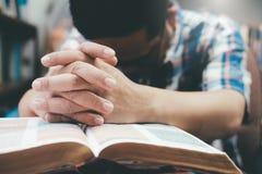 Man att be, händer som tillsammans knäppas fast på hennes bibel royaltyfria foton
