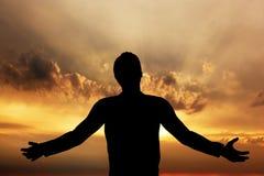 Man att be och att meditera i harmoni och fred på solnedgången royaltyfria foton