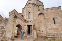 Man att be på ingången av den Jvari kloster som byggs i det 6th århundradet i Mtskheta, Georgia Världsarvplats av UNESCO Royaltyfri Foto