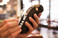 Man att betala med NFC-teknologi på kreditkort, i restaurang, lodisar Arkivbild