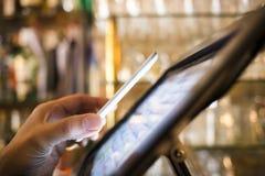 Man att betala med NFC-teknologi på mobiltelefonen, i restaurang, b Royaltyfri Foto