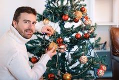 Man att dekorera ett julträd med guld- bollar arkivfoto