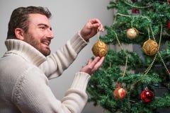 Man att dekorera ett julträd med guld- bollar arkivbild