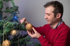 Man att dekorera ett julträd med guld- bollar royaltyfria bilder