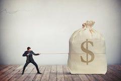 Man att dra på en stor påse för rep av pengar royaltyfri fotografi