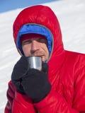 Man att dricka från en råna i bergen arkivfoto