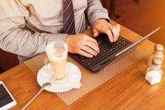 Man att dricka kaffe i kafé och att använda bärbara datorn Royaltyfria Foton