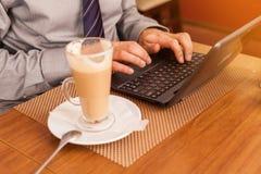 Man att dricka kaffe i kafé och att använda bärbara datorn Arkivbild