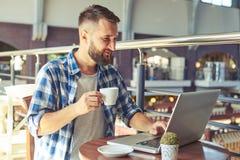 Man att dricka kaffe och att använda bärbara datorn i kafé Royaltyfria Bilder
