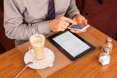 Man att dricka kaffe och att använda minnestavlan och mobilen Fotografering för Bildbyråer