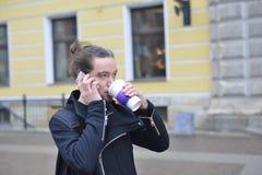 Man att dricka kaffe och samtal på telefonen Arkivbild