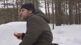 Man att dricka te från termoset i en vinterskog arkivfilmer