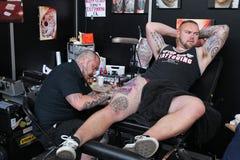 Man att få en tatuering, på en tatueringstudio arkivfoton
