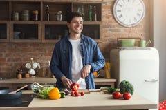 Man att förbereda läcker och sund mat i det hem- köket royaltyfri fotografi